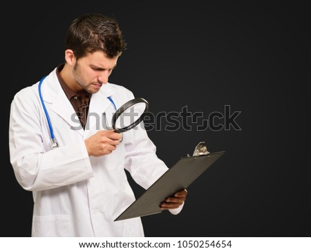 Young Doctor Looking Through Magnifying Glass On Black Background