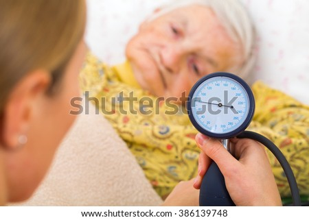 Young doctor measures the elderly woman blood pressure - stock photo