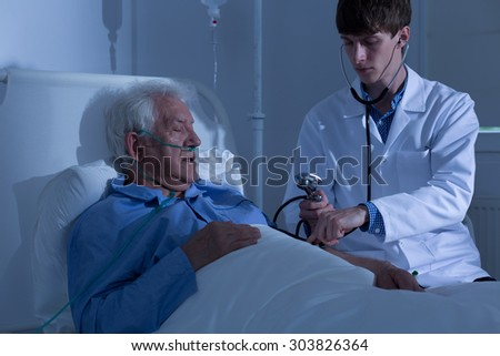 Young doctor measuring blood pressure in hospital - stock photo