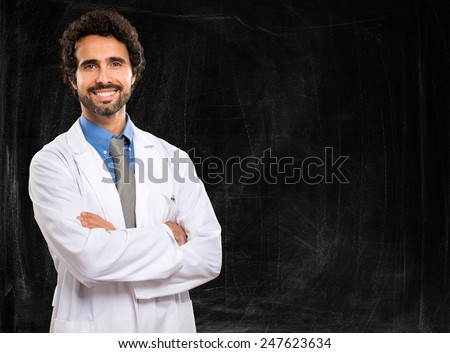 Young doctor on a chalkboard background - stock photo