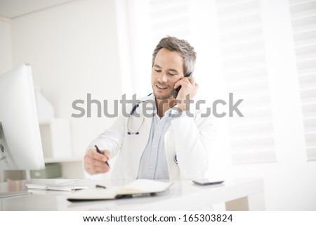 young doctor on phone at his office - stock photo
