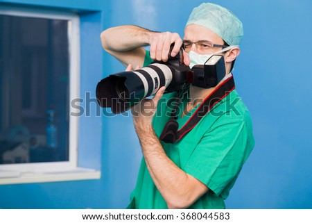 Young doctor photographing the medical procedures during surgery.