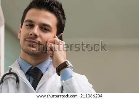 Young Doctor Talking On The Phone - stock photo