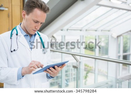 Young doctor using his tablet pc at the hospital