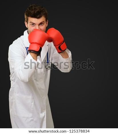 Young Doctor Wearing Boxing Gloves Covering Mouth On Black Background - stock photo