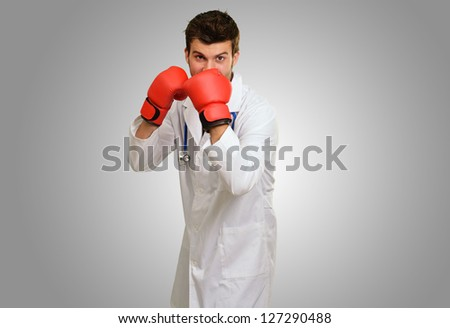 Young Doctor Wearing Boxing Gloves Covering Mouth On Grey Background - stock photo