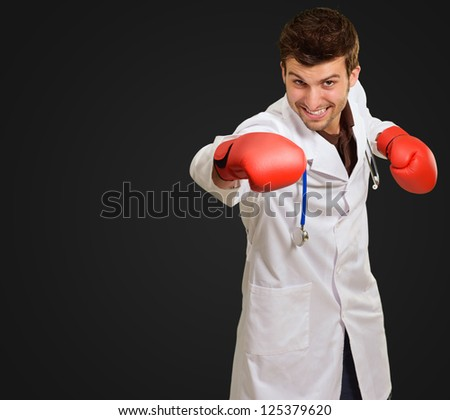 Young Doctor Wearing Boxing Gloves On Black Background - stock photo