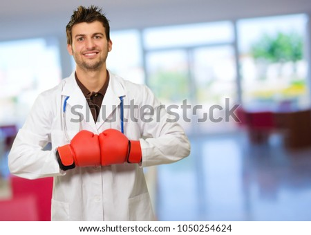 Young Doctor Wearing Boxing Gloves With Hands Together, Indoor
