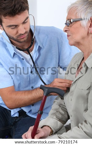 Young doctor with elderly patient - stock photo