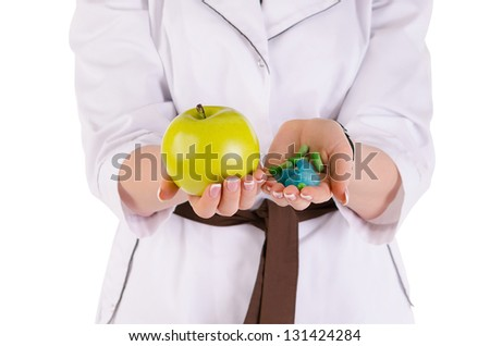 Young doctor with pill and apple isolated over white background - stock photo