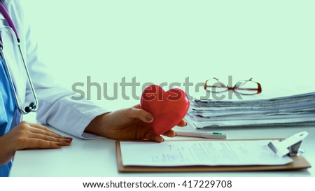 Young doctor with red heart symbol sitting at desk  - stock photo
