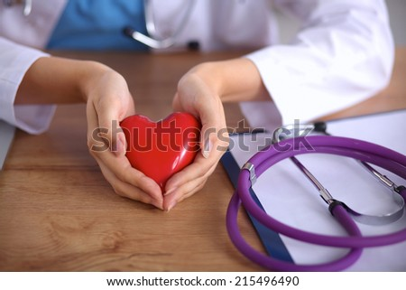 Young doctor with red heart symbol sitting at desk isolated - stock photo