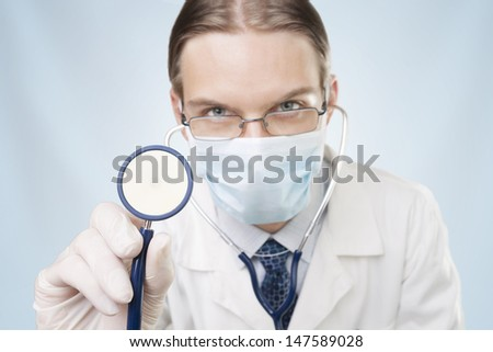 Young doctor with stethoscope listening to your heart. - stock photo