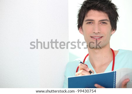 Young doctor writing in notebook - stock photo