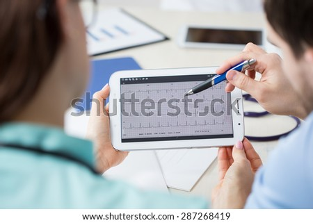 Young doctors analysing electrocardiogram on a tablet