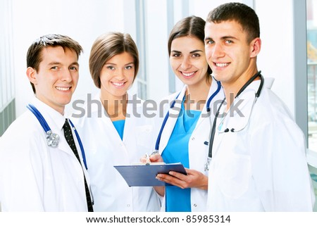 Young doctors are standing inside the hospital and looking at camera - stock photo
