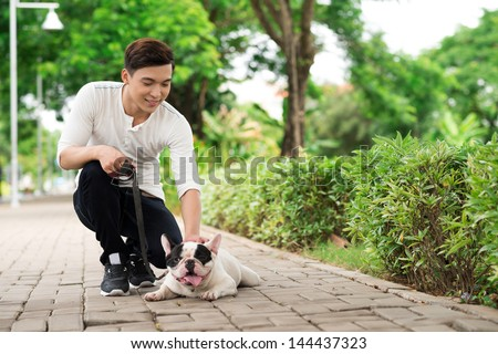 Young dog-owner and his French bulldog spending a summer day in park