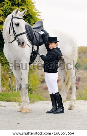 Young dressage rider with big gray horse - stock photo