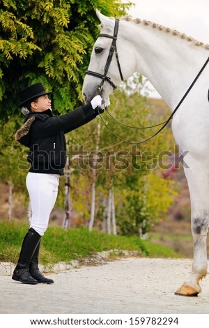 Young dressage rider with big sport horse - stock photo