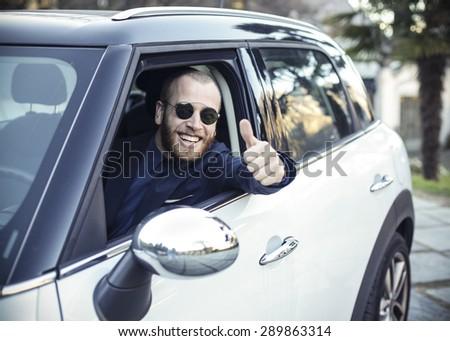 Young driver showing thumb up gesture - stock photo