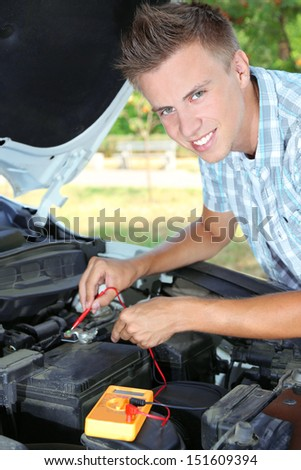 Young driver uses multimeter voltmeter to check voltage level in car battery - stock photo