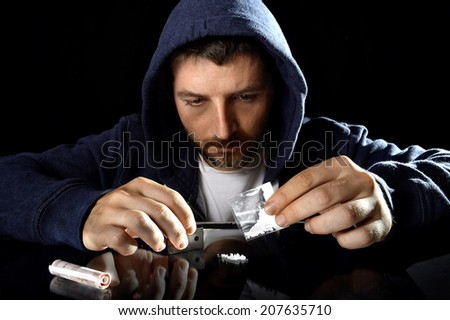 young drug addict man on hood alone ready preparing cocaine lines pouring gram bag on mirror with rolled banknote in moody and grunge lighting studio setting