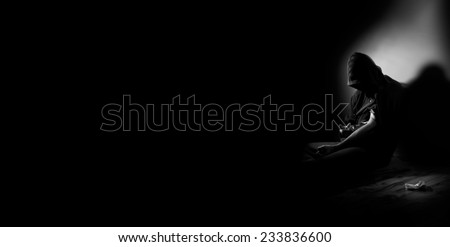 Young drug addict sitting on the floor, taking intravenous dose of heroin - stock photo