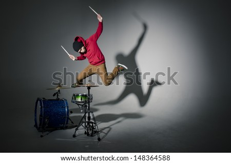 young drummer jumping while playing - stock photo