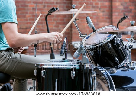 Young drummer playing at drums set - stock photo
