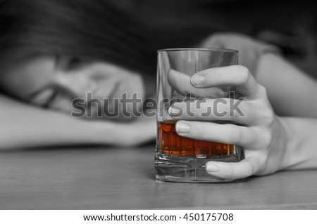 Young drunk woman holding a glass of whiskey - stock photo