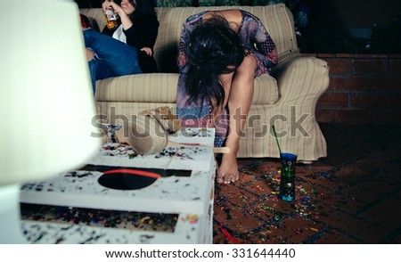 Young drunk woman holding her head sitting in the sofa in a outdoors party. Fun and alcohol and drugs problems concept. - stock photo