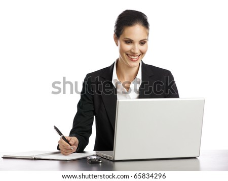 Young, dynamic businesswoman working with laptop and holding a pen