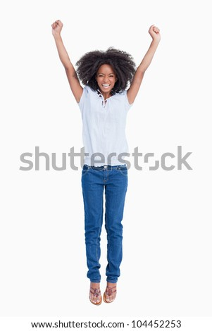 Young dynamic woman raising her arms above her head against a white background