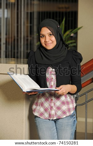 Young Eastern Student holding a book inside a College Building - stock photo