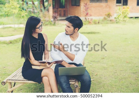 Young education couple sitting on the bench talk about study in the outdoors and good weather.