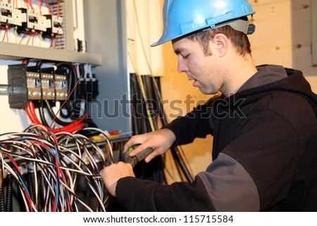 Young electrician at work - stock photo