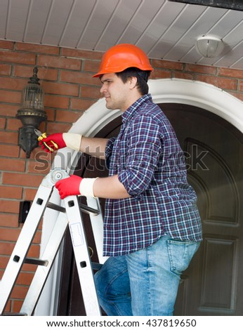 Young electrician changing bulb in outdoor lamp on house wall