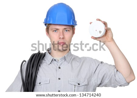 Young electrician holding smoke alarm - stock photo