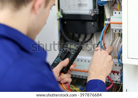 Young electrician measuring voltage in fuse board - stock photo