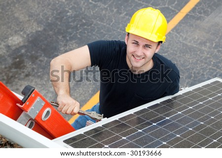 Young electrician on a ladder installing solar panels. - stock photo