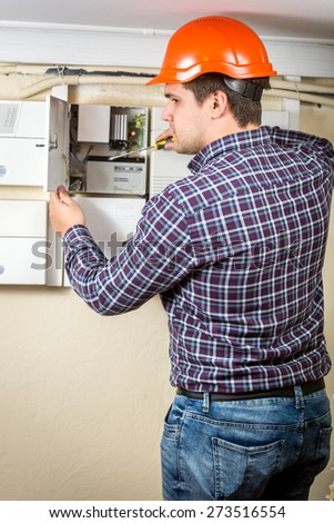 Young electrician repairing electrical board at home - stock photo