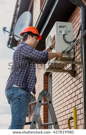 Young electrician standing on step ladder and repairing air conditioning system - stock photo