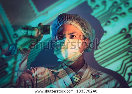 Young electronic engineer holding computer microchip  - stock photo
