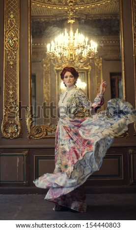young elegance woman with flying dress in palace room