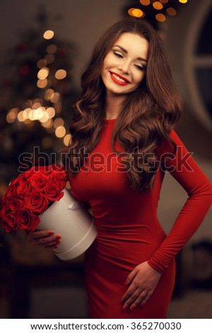 Young elegant beautiful lady in red dress with bouquet of red roses posing in evening interior - stock photo