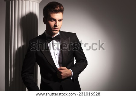 Young elegant business man posing near white column while fixing his jacket.