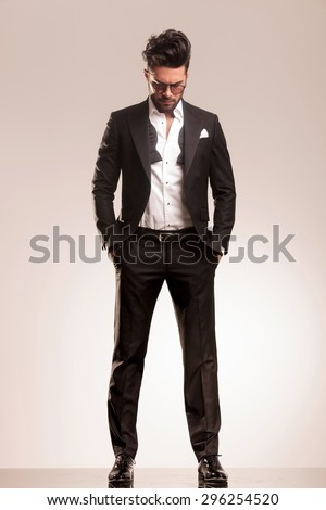 Young elegant business man standing with both hand in his pocket while looking down. - stock photo