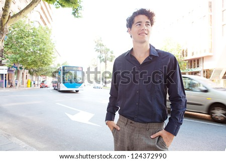 Young elegant businessman standing in a large avenue in the city with his hands in his pockets and with traffic in the background, smiling.