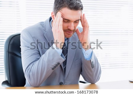 Young elegant businessman with severe headache sitting at office desk