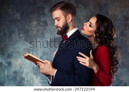 Young elegant couple in evening dress portrait. Man reading book and woman trying to attract and embrace him. - stock photo